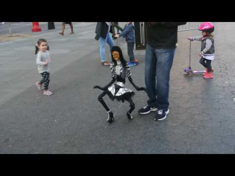 Street performer Skelesha Puppet Master has fun with the kids In Union Square park NYC Oct 2016