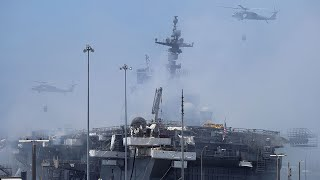 US Navy and firefighters battle for second day to save burning warship in San Diego