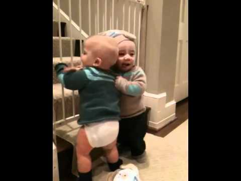 Twin baby boys hugging, laughing & tackling eachother