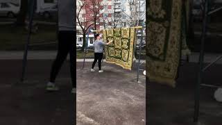 Женщина выбивает ковёр на детской площадке