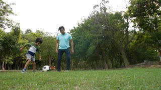 Cute Indian child having fun while playing football with his father in a park - leisure time