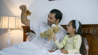 Indian father playing with daughter with her toys before going to sleep.