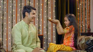 Young Indian siblings happily performing Raksha Bandhan / Bhai Dooj traditions