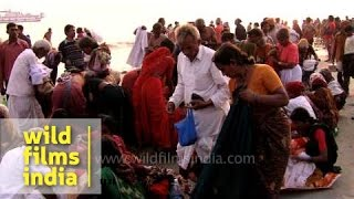 Indian pilgrims putting their clothes on after a holy dip