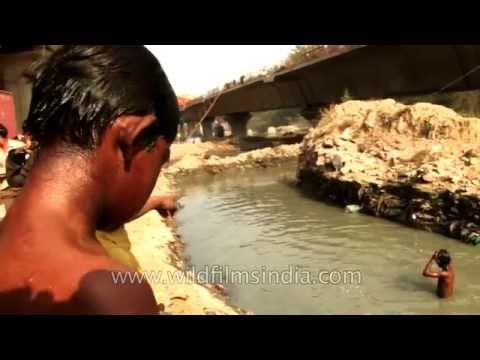Young rag-pickers dive into dirty water to beat Delhi's heat