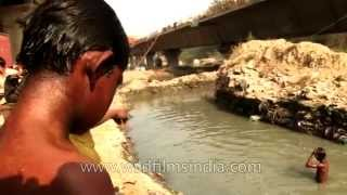 Repeat youtube video Young rag-pickers dive into dirty water to beat Delhi's heat