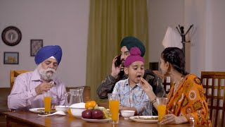 Indian family having breakfast together at a dining table. Surd army man on a phone call