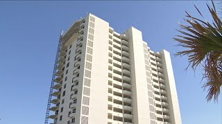 Man fell about 100 feet while working on balcony at high-rise complex.