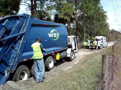 Garbage truck stuck in a sand pit.