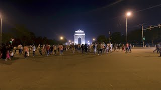 Timelapse of vehicles moving in fast motion and people crossing road at India Gate