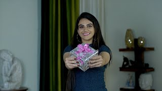 Beautiful young female smiling and offering Valentine's special gift to the camera