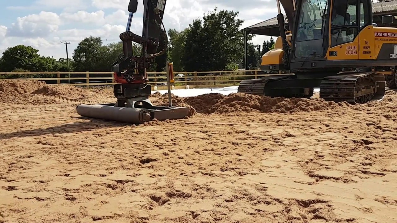 Laser grading fibre sand in a horse arena ( manege) construction with  rototilt and a grading beam