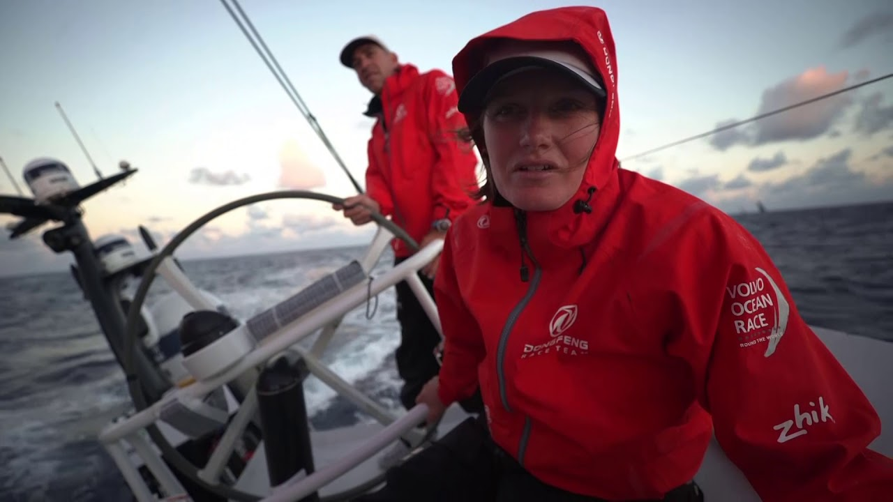 "Dusk. Light winds. Stu on the helm with MAPFRE behind him. Dawn. Stu: Nice to be back on board and sailing again. Interesting night; clouds, rain. Upwind sailing; all the boats close. Settling into routine again. Sometime today we'll tack. Marie chews something. Sunrise. Marie: Stu has been something like 8 times in the Volvo Ocean Race. One of the most experienced. So lots of people call him, ""Magic Stu."" Good news that he's back with the team. Stu on the helm."
