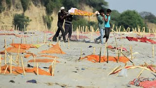 video: Covid victims' bodies buried in shallow mass graves along banks of India's Ganges