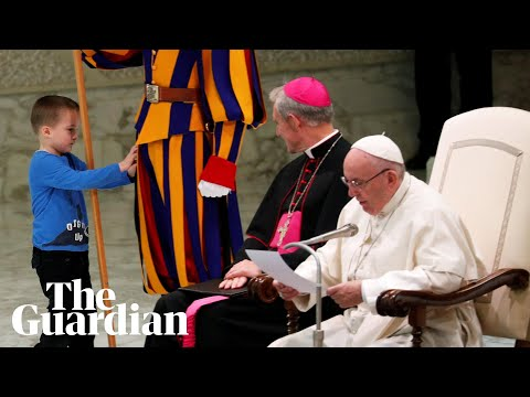 Pope Francis chuckles as boy climbs on stage and interrupts speech