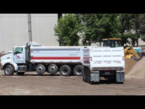 Work Trucks Backing up with a dump truck dumping into a pile