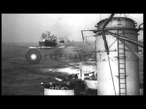 A burning cargo vessel and a convoy of ships moves towards a beach in Salerno, It...HD Stock Footage