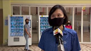 自动派发机领取口罩 工作人员从旁协助