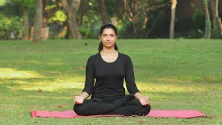 A young girl practicing bhastrika pranayama outside in a park