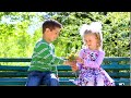 Boy Is Giving Flowers To Pretty Girl  Young Couple In Love  Two Adorable Children In Sunny Park  Def