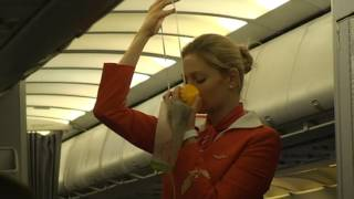 Aeroflot stewardess. Lady in exciting red dress explains emergency procedures.