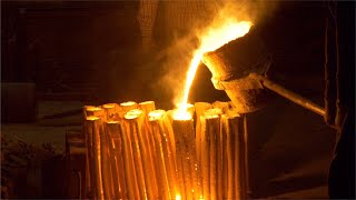 The molten metal is poured into the molds from a ladle in a iron and steel plant