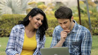 Young happy couple looking at laptop screen and talking in a park on a bright sunny day