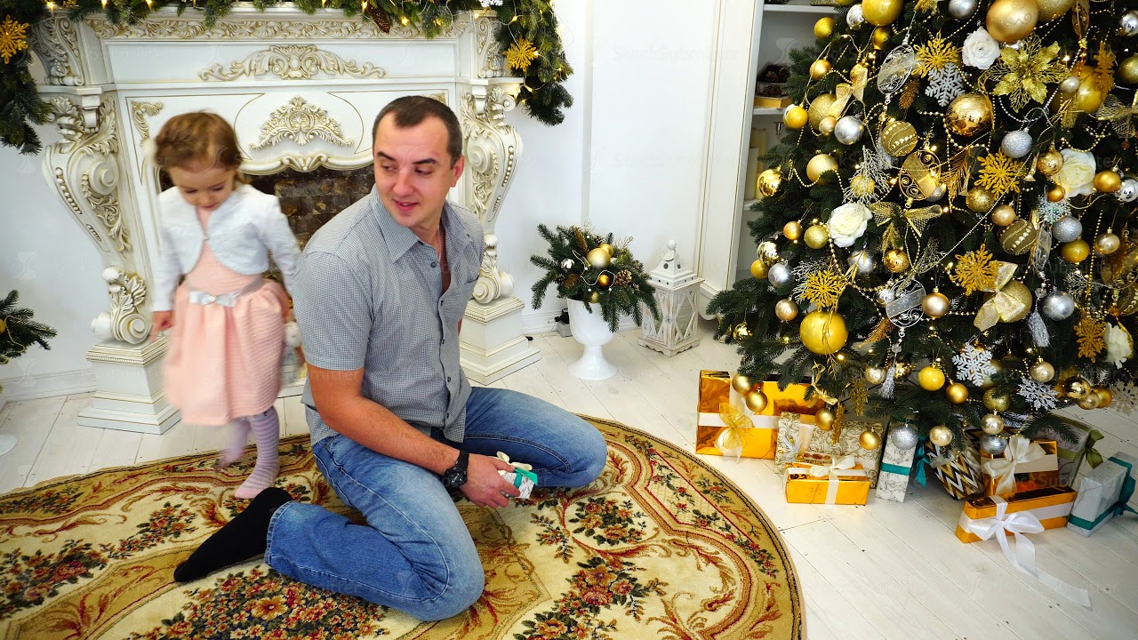 young adult dad with little daughter exchange gifts and hugging each other in large room on