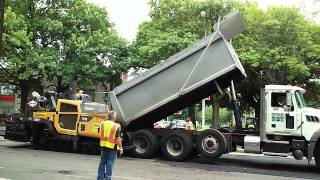 An NYC DOT Dump Truck Feeds An Road Resurfacing Machine During Re-pavement Processes On Morrison Ave