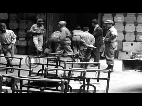 Workers handle Japanese treasure under supervision of US soldier at a warehouse i...HD Stock Footage