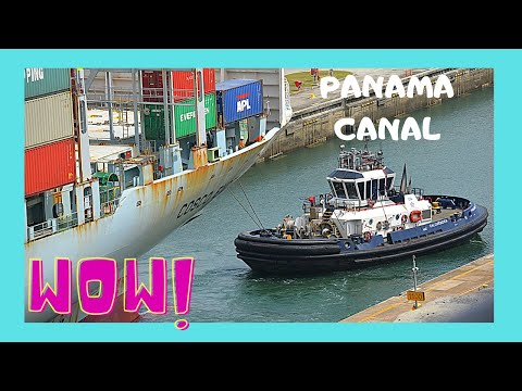THE PANAMA CANAL, huge CARGO SHIP crossing and LOCOMOTIVES guiding it through
