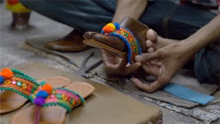 Cobbler making a beautiful bright colored sandal