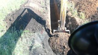 Экскаватор копает траншею под водопровод