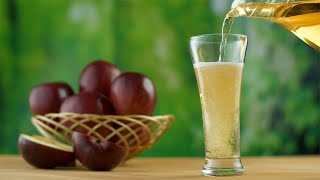 Hands pouring homemade apple juice into a glass from a jug - ready to drink, healthy living
