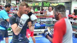 Amateur boxer hitting pads with Jeff Mayweather inside the Mayweather Boxing Club