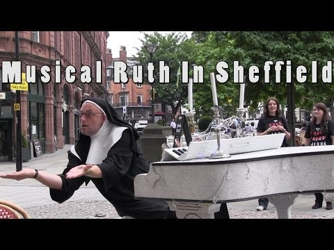 Musical Ruth Goes Mad - Man Dressed As Nun Driving a Piano