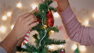 Closeup shot of a couple decorating Christmas tree