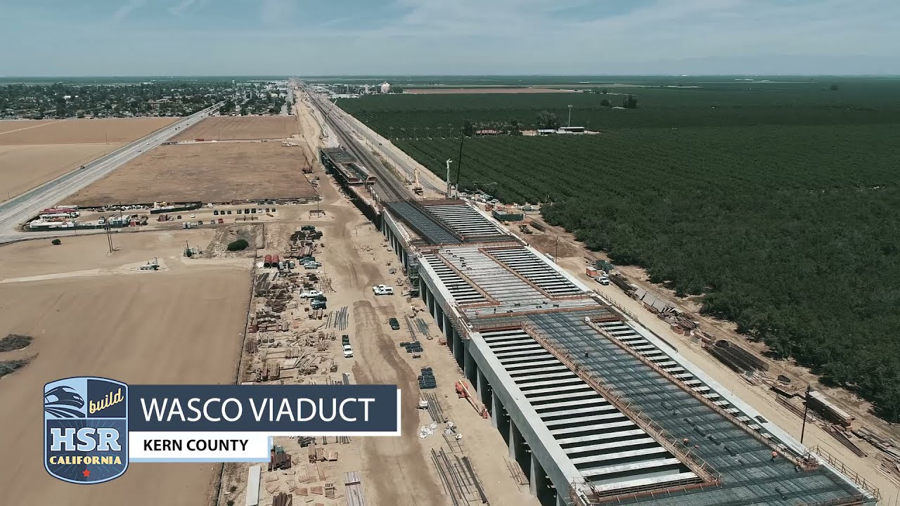 April 2021 drone footage of the Wasco Viaduct.  www.BuildHSR.com (Projects) ....  OVERVIEW The Wasco Viaduct will take high-speed trains over the existing BNSF freight tracks and will be nearly 2,000 feet long when complete.  LOCATION The Wasco Viaduct is located south of the City of Wasco near Jackson Avenue.  CURRENTLY The Wasco Viaduct continues to take shape with plenty of work happening across the entire structure. To the north, crews are placing temporary forms for future sound walls that will reach 34-feet high. Close by, crews are placing the bulk head on the end of the section footing in preparation for a concrete pour. Nearly 290 cubic-yards will be needed for the footing. At the pergola section crews continue to tie rebar on the upper edge girders while carpenters are placing forms for the upper edge girder for concrete placement.