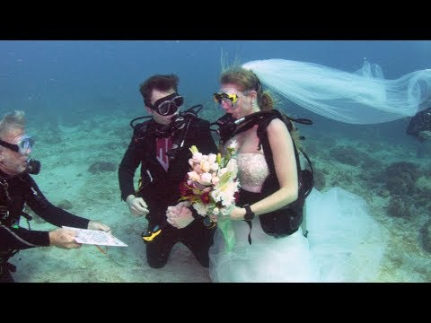 In sea sickness and in health Couple stage underwater wedding ceremony