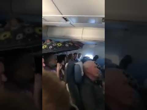 Los pasajeros de un avión se protegen de las goteras en cabina con unos paraguas