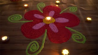 Beautiful shot of a colorful rangoli decorated with glowing oil lamps on Diwali/Dipavali