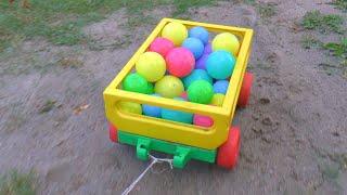 Сеня перевозит разноцветные мячики на машине и смотрит как они сыпятся через трубу