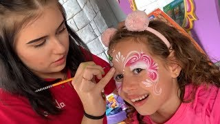 Valentina brincando e pintando o rosto de unicórnio