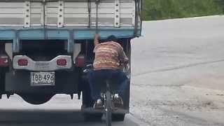 Family Travel Blog-Dangerous Highway Driving-Guy On Bike Hangs Onto Truck (Colombia)