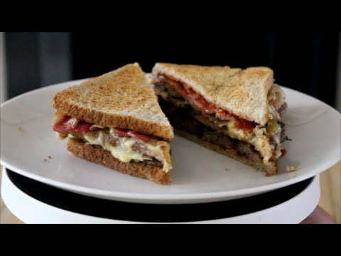 A Breakfast Sandwich With Sausage Bacon Eggy Bread Mushrooms Cheese