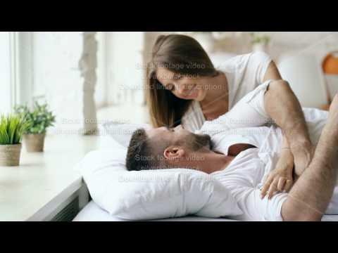 Young beautiful and loving couple wake up at the morning. Attractive woman kiss and hug his husband thumbnail
