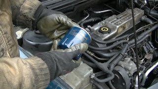 Should you tighten the oil filter by hand or with the wrench?