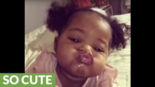 Baby humorously puckers up for adorable kiss