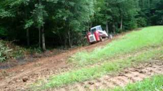 Skid steer grading a muddy slope