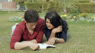 Pan shot of a couple lying in a park and reading book on a sunny day